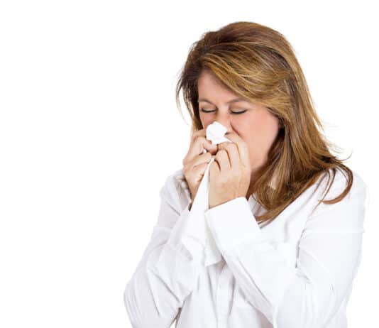 Closeup portrait of a miserable, sick adult woman with allergy, cold, blowing her nose with paper tissue, isolated on white background. Human face expressions. Flu season, vaccination, prevention.