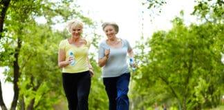 Portrait of two senior females running outdoors