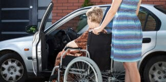 Girl helping senior woman on wheelchair getting into a car, horizontal