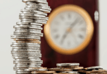 a stack of coins and a clock in the background